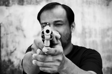 black and white of man holding gun and pointing his gun revolver. Selectively concentrated on the front of the gun.