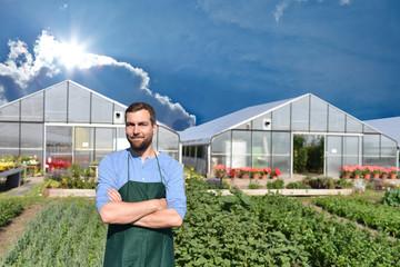 Portrait erfolgreicher Gärtner/ Bauer - im hintergrund Gewächshaus und Gemüsefeld // successful farmer in front of a greenhouse