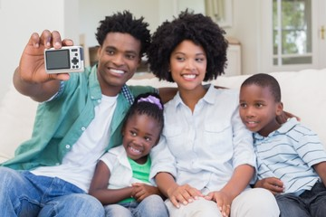 Happy family taking a selfie on the couch