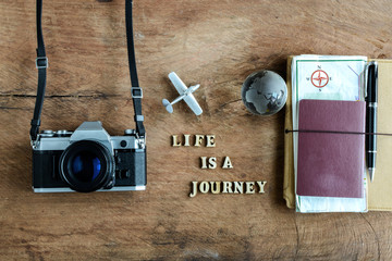 Notebook with map, passport and camera on wooden background