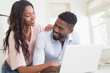 Happy couple using their laptop