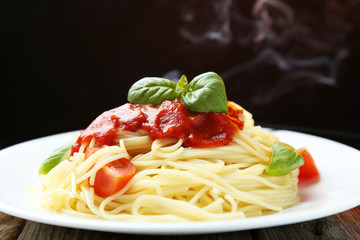 Spaghetti with tomatoes and basil on plate on grey wooden backgr