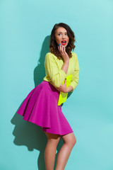 Surprised young woman in pink skirt and lime green blouse holding hand on chin and looking away. Three quarter length studio shot on teal background.