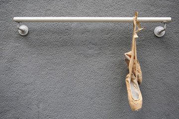 Old Used Ballet Shoes Hanging on metal rod