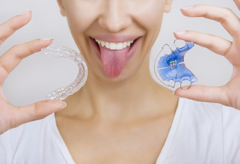 Smiling girl Holding Retainer for Teeth and Tooth Tray
