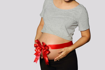 Belly of pregnant woman with red ribbon on gray background.