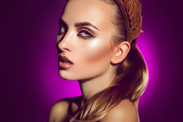 beautiful young woman with professional makeup on purple backgro