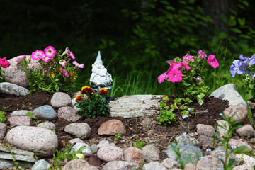 Flowerbed in a garden of flowers, embellished with stones and dw