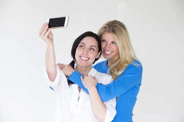 Same sex female couple taking a selfie using a mobile phone in front of a plain background