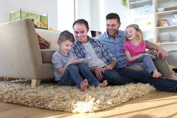 Same sex male couple sitting on the floor of their front room with their children, helping them do their homework