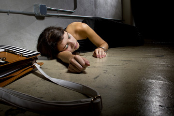 female crime victim laying on the street floor or passed out drunk