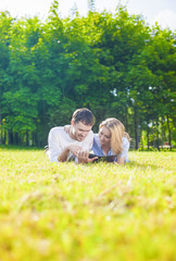 Happy Caucasian Couple in Love Lying on the Grass Outdoors. Read