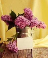 Bouquet of lilac flowers in a metal bucket on a wooden table against yellow fabric with a white empty photograph. Decor in ancient style