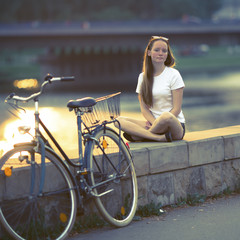 Lovely teen girl with the bike sits on the waterfront (film cross process style)