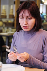 Woman holding two forks in the restaurant