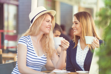 Two cheerful young girlfriends sitting in a cafe drinking coffee and relaxing after shopping