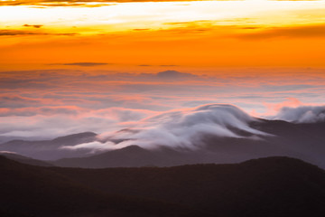 The amazing sunrise along the Blue Ridge Parkway shows the clouds hugging the mountain ridges.