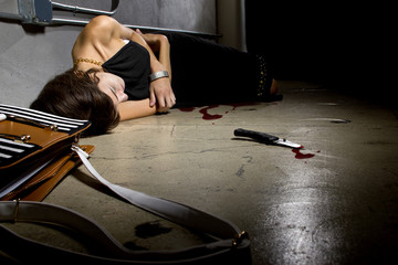 female murder victim laying on a dark alley with a bloody knife
