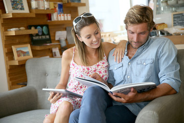 Trendy couple in coffee shop reading magazine sitting in sofa
