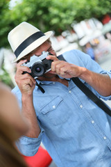 Trendy guy with hat taking picture of woman with vintage camera