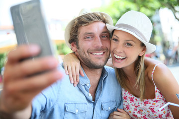 Couple of tourists taking selfie picture with smartphone