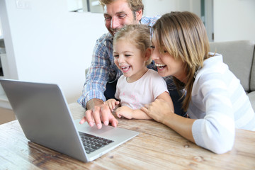 Parents with little girl laughing in front of laptop computer