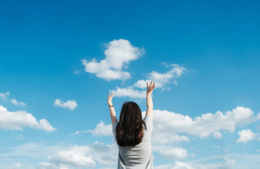 A young woman stretches her hand towards the sky