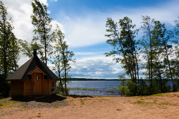 Summer landscape with lake and wooden house