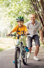 Little boy learn to ride bicycle with his father