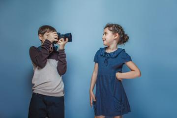 Boy teenager European appearance photographs teen  girl on a gra