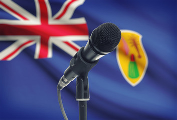 Microphone on stand with national flag on background - Turks and Caicos Islands