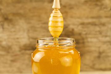 glass jar of honey with drizzler on wooden background