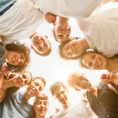 Group of ten young teenagers friends gathered to form a circle in the park, embraced each other. Group seen from bottom to top, during a summer day in a park at sunset