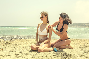 Young girls using sun cream at the beach