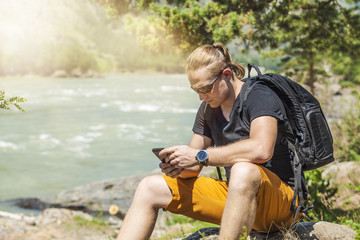 A tourist with a phone and a backpack on the mountains