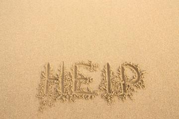 """The inscription on the sand beach """"Help"""""""
