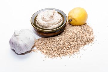 Tahini sobre fondo blanco con ingredientes de la receta