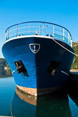 The bow of a blue greek ship in harbor at morning