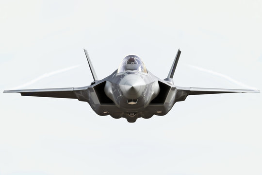 F35 front view close up flying to the camera with chem trails