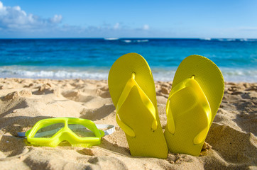 Wall Mural - Yellow flip flops with swim glasses on the sandy beach