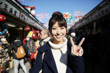 東京観光イメージ  浅草寺 仲見世通りでピースをする女性