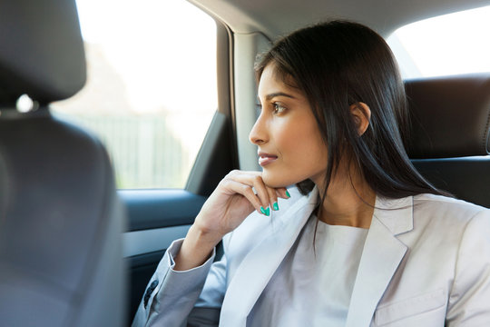 indian business woman sitting in car backseat