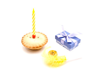 Cupcake with yellow birthday candle, whistle and gift on white