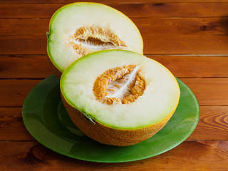 Two halves of a melon on green plate