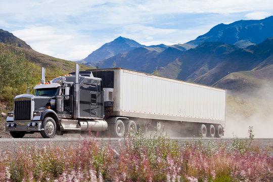Semi truck on dusty road in mountain landscape