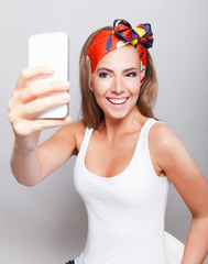 Smiling pretty woman taking a selfie with mobile phone