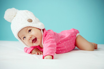 Little baby in knit winter clothing closing face with knitted be