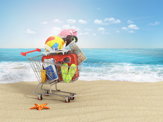 Shopping cart with beach accessories on the beach line. Summer shopping.
