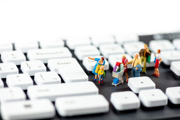 Friendly miniature family looking at computer keyboards. Technology concept