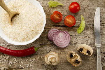 Cooking rice on aged wooden background. Cut onion, mushrooms. Chile pepper, cherry tomatoes, green salad. Healthy eating, diet, vegetarianism.
